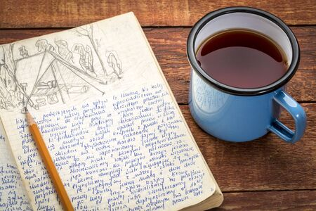 Kayak expedition journal with a metal cup of hot tea on a rustic picnic table  - handwriting and drawing in pencil. Travel log from paddling trip across north eastern Poland written by me, photographer, in August 1974.