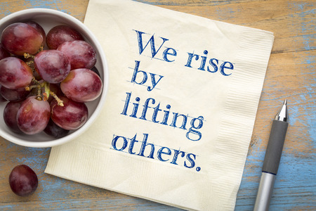 We rise by lifting others wisdom quote - handwriting on a napkin with fresh grapes Foto de archivo