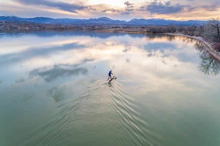 paddling stand up paddleboard at dusk on a kae of foothills of Rocky Mountain in Colorado, early spring scenery, aerial view Stock Photo