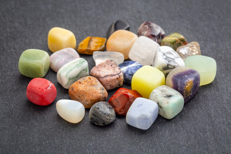 a pile of polished, semiprecious, colorful gemstones against gray slate stone Imagens