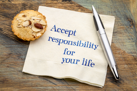 Accept responsibility for your life - inspirational handwriting on a napkin with an almond cookie Banco de Imagens