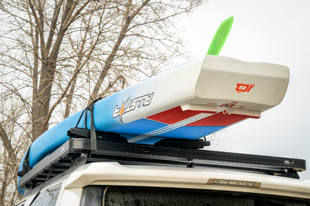 Fort Collins, CO, USA - April 7, 2018: A racing stand up paddleboard by Starboard (2018 All Star model) on roof racks of Toyota 4Runner.