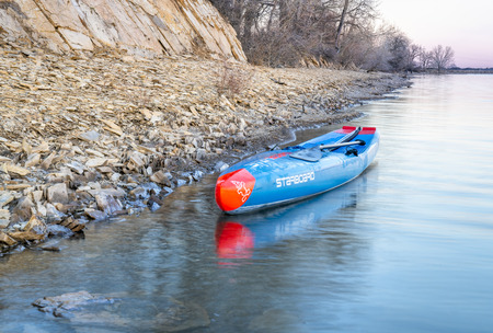 Fort Collins, CO, USA - April 22, 2018: After paddling workout - a racing stand up paddleboard (2018 All Star by Starboard) on the rocky shore of a lake in northern Colorado. Editöryel