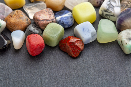 polished, semiprecious, colorful gemstones against gray slate stone with a copy space