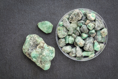 raw emerald gemstones (mineral beryl) with inclusions mined in Brazil on a gray slate stone Stock Photo