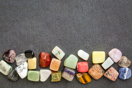 a row of polished, semiprecious, colorful gemstones against gray slate stone with a copy space