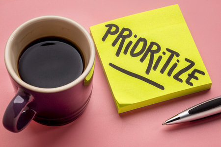 prioritize advice or reminder - handwriting on a sticky note with a cup of coffee Stock Photo