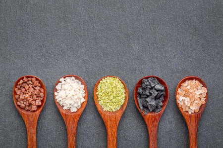 colection of colorful sea salts from different parts of the world, top view of wooden tea spoons against slate stone with a copy space