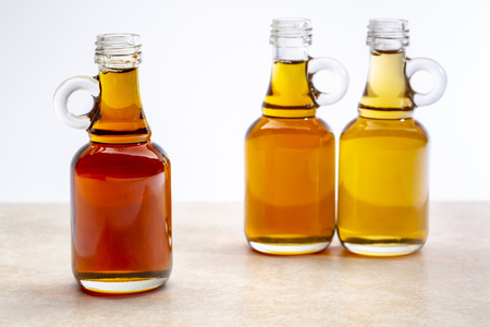 sampler of pure maple syrup (golden, amber and gold) - three small glass bottles on a ceramic background