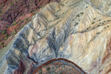 Aerial view of colorful rock formation and steep cliff along Onion Creek in Moab area, Utah