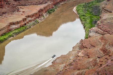 A jetboat transporting kayaks upstream of Colorado River below Moab in Utah Stock Photo