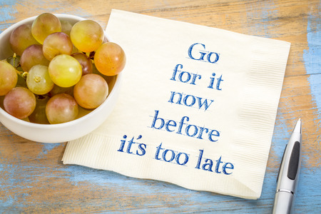 Go for it before it is too late - handwriting on a napkin with fresh grapes