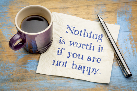 Nothing is worth it if you are not happy - handwriting on a napkin with a cup of coffee