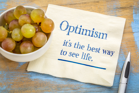 optimism - best way to see life, inspirational handwriting on a napkin with fresh grapes Stock fotó