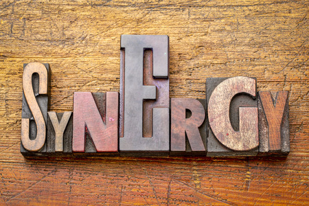 synergy - word abstract in vintage letterpress wood type against rustic wooden background