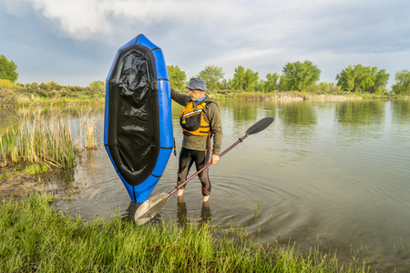 a senior male with a blue pacraft (one-person light raft used for expedition or adventure racing) on a lake shore in spring scenery Stock Photo