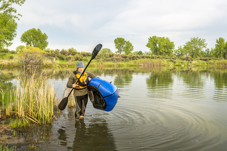 senior male carrying a packraft(one-person light raft used for expedition or adventure racing) on a lake shore in Colorado in springtime scenery