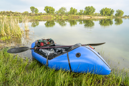 a blue pacraft (one-person light raft used for expedition or adventure racing) with a kayak paddle on a lake shore in spring scenery