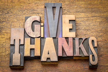give thanks - word abstract in vintage letterpress wood type (mixed fonts) against rustic wooden background - Thanksgiving concept Stock Photo