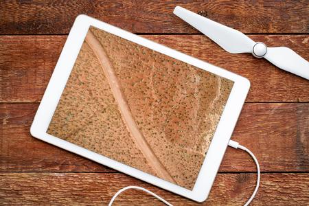 desert road in Moab area, Utah - reviewing an aerial image on a digital tablet