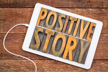 positive story - word abstract in vintage letterpress wood type on a digital tablet against rustic wood Stockfoto