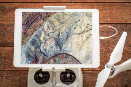 Colorful rock formation and stream along Onion Creek in Moab area, Utah - reviewing an aerial image on a digital tablet mounted on a drone radio controller