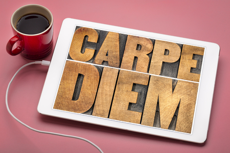 Carpe Diem  - enjoy life before it is too late, existential cautionary Latin phrase by Horace -  text in vintage letterpress wood type printing blocks on a digital tablet with a cup of coffee Stock Photo
