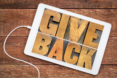 give back word abstract in vintage letterpress wood type on a digital tablet Stock Photo - 102250073