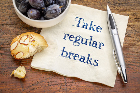 Take regular breaks advice  - handwriting on a napkin with grapes and cookie Stock Photo