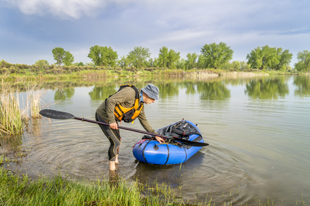 a senior male launching a packraft (one-person light raft used for expedition or adventure racing) on a lake shore in spring scenery Stock Photo - 102195473