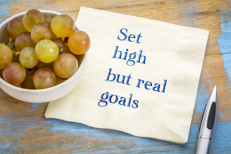 Set high, but real goals - motivational handwriting on napkin with fresh grapes Stock Photo - 102769325