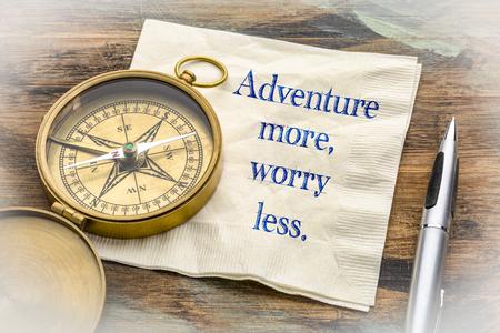 Adventure more, worry less  - inspiraitonal handwriting on a napkin with an antique brass compass