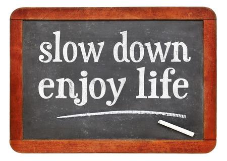 Slow down, enjoy life - white chalk text on a vintage slate blackboard