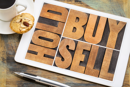 buy, hold, sell - investing concept - word abstract in vintage letterpress wood type on a digital tablet with a cup of coffee Stock Photo