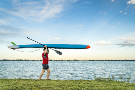 A senior paddler walking with a racing stand up paddleboard on lake shore in Colorado