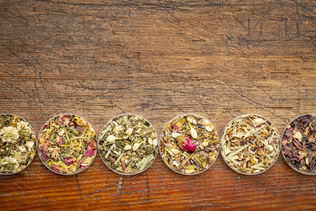 Chinese herbal tea sampler collection - a row of round bowls (Petri dish) on a rustic wood with a copy space Stock Photo