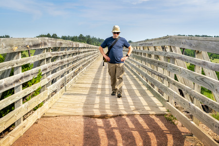 senior male walking on old railroad trestle acroos Niobrara River , now a multi-use recreational Cowboy Trail in northern Nebraska Stock Photo - 102952601