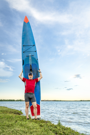 A senior paddler with his racing stand up paddleboard on a lake shote in Colorado