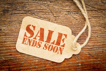 Sale ends soon sign - red stencil text on a cardboard price tag against rustic wood