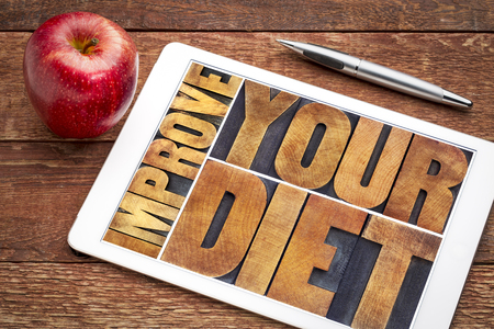 improve your diet - healthy lifestyle concept - word abstract  in vintage letterpress wood type printing blocks on a digital tablet with an apple