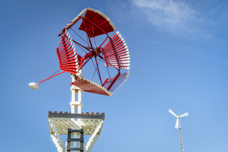 Antique windmill for water pumping in Amercian prairie against blue sky with a modern wind turbine in background