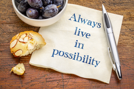 Always live in possibility mantra or reminder - inspirational handwriting on a napking with fresh grapes