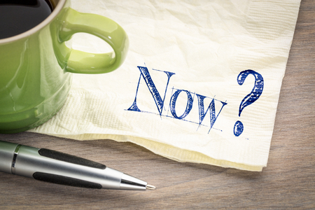 Now? A question handwritten on a napkin with cup of coffee.