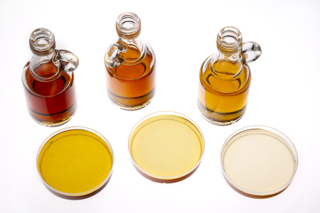 sampler of pure maple syrup (golden, amber and gold) - three small glass bottles and small bowls on white Banco de Imagens