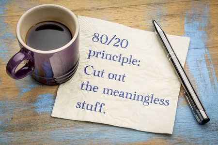 80-20 principle: cut out the meaningless stuff - inspirational handwriitng on a napkin with a cup of coffee