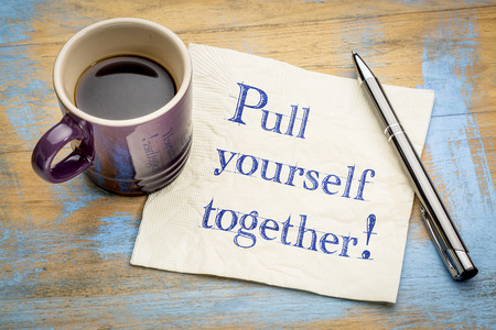 Pull yourself together - handwriitng on napkin with a cup of coffee