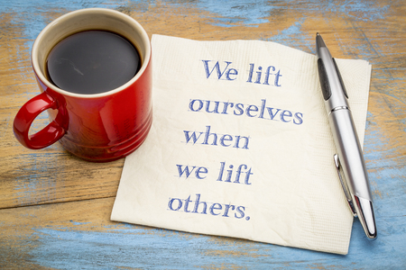 We lift ourselves by lifting others  - inspiraitonal handwriitng on napkin with a cup of coffee