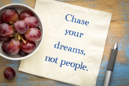 Chase your dreams, not people - inspirational handwriting on a napkin with grapes