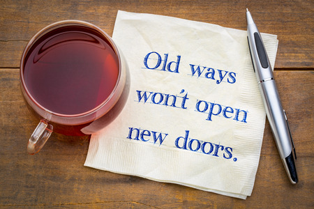 Old ways will not open new doors - handwriting on a napkin with a cup of tea.