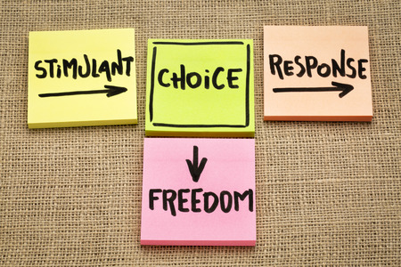 freedom concept as a choice made bettwen stimulant and response - handwriting on sticky note against burlap canvas